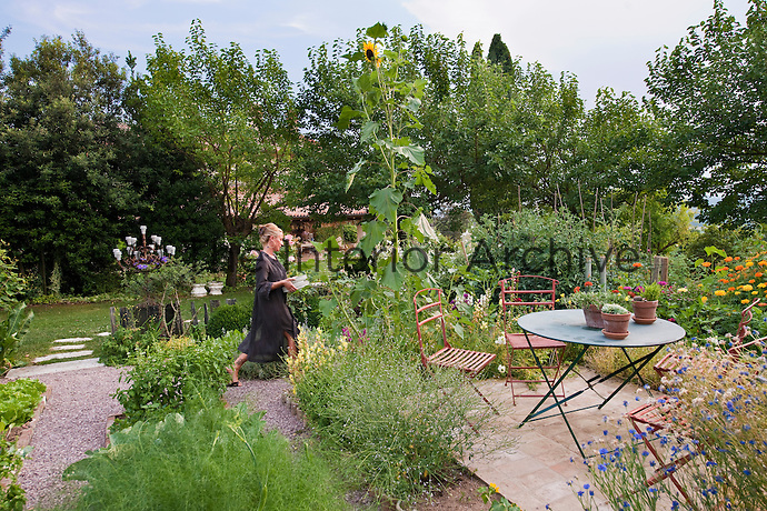 A woman carrying plates through the herb garden with a small patio with table and chairs