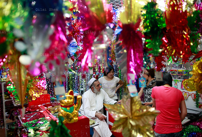 A muslim trader talk with stall owners selling holiday decorations at the Yiwu International Trade City in Yiwu, Zhejiang Province, China on Sunday, 11 September 2011.   As the trading hub for small and medium manufacturers and exporters in the Yangtze River Delta region, Yiwu faces an uncertain future as export orders decline due to the slow economic recoveries of China's two largest trading partners, Europe and the United States
