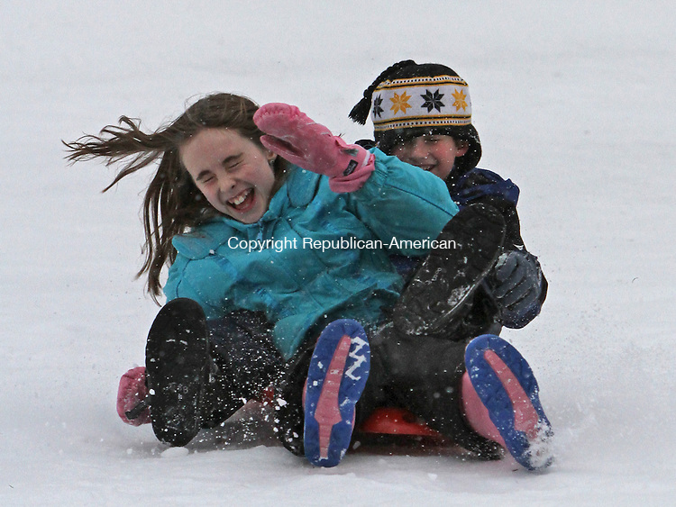 Torrington, CT-122912MK02 Allison Madeau (11, Torrington) and Spencer Buechele( 12 Cape Cod, MA.) struggle to remain on their sled down as they giggle down the slope at Major William E. Besse Park in Torrington on Saturday afternoon.  Dozens of snow enthusiasts enjoyed the light fresh falling snow on the hill before heading home ahead of the forecasted storm which dumped several inches in Litchfield County. The temperatures are expected to remain in the twenties today which could provide for continued snow sport enjoyment . Michael Kabelka / Republican-American
