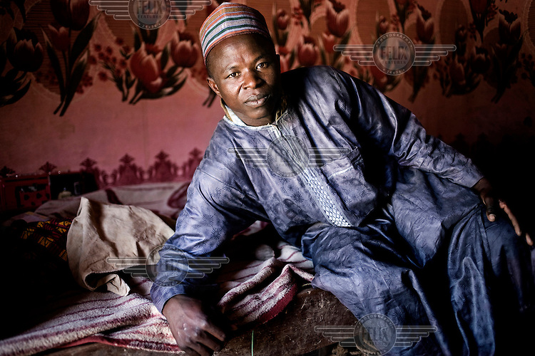 Ouma's new husband, Hamidou, poses in his bedroom. In Niger, three out of every four women are married before the age of 18. These marriages are often arranged between the girl's parents and her future husband to be, who has to pay for the girl with a dowry.