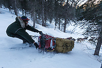 Mike Ellis does a control slide down a hill after leaving the Finger Lake checkpoint, Monday March 3 during the Iditarod Sled Dog Race 2014.<br /> <br /> PHOTO (c) BY JEFF SCHULTZ/IditarodPhotos.com -- REPRODUCTION PROHIBITED WITHOUT PERMISSION