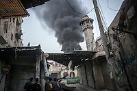 In this Sunday, Nov. 04, 2012 photo, rebel fighters watch to the background as smoke rises after Syrian artillery fired a missile at the rebel's position during heavy clashes in the nearby Qastal Al-Harami battlefield in the Jdeide district of Aleppo, the Syrian's largest city. (AP Photo/Narciso Contreras).