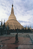 A solitary monk shuffles past the giant main dome of the Shwedagon Pagoda in Rangoon, Burma, shortly after dawn and before the crowds that throng the main terrace every day have arrived.