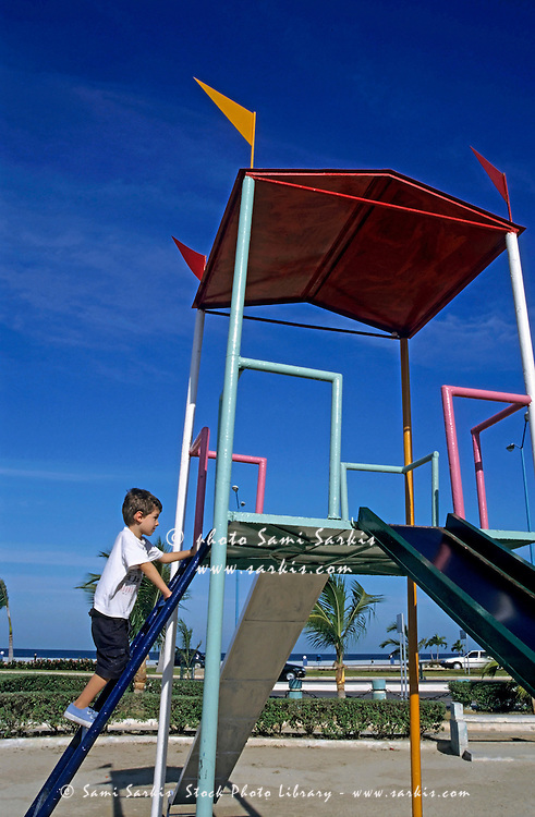 Young boy on a slide in a playground, Campeche, Mexico.