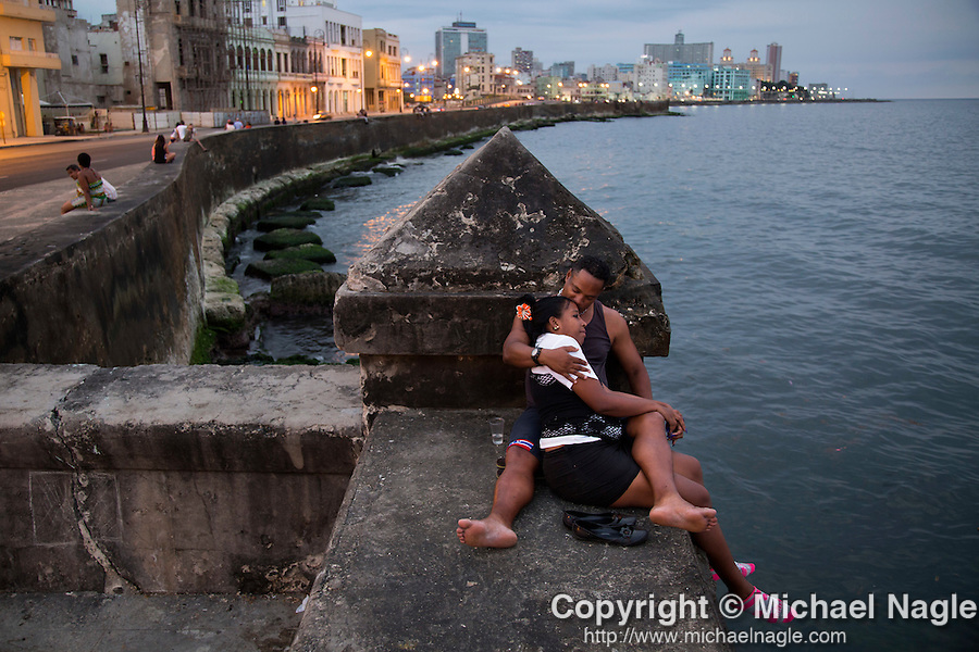 HAVANA, CUBA -- MARCH 24, 2015:   A couple sits on the seawall along the Malecon in Havana, Cuba on March 24, 2015. Photograph by Michael Nagle
