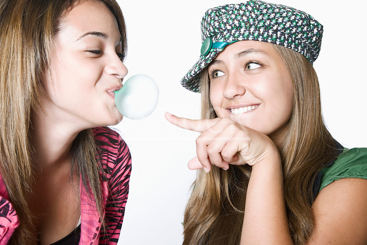 Teenage girl blowing bubble, friend bursting it