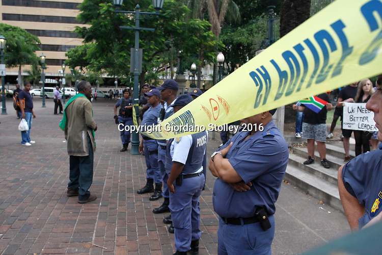 DURBAN - 11 February 2016 - On the very day that South Africa's President Jacob Zuma was due to deliver the state of the nation address to parliament 2000 kilometres away in Cape Town, a small group of protesters staged a protest for him to go. Police had to erect a cordon to keep them safe. Passing supporters of the South African president heckled those who want him to leave office. Zuma the third president of the country since the ruling African National Congress took power in 1994 has becoming increasingly unpopular amid allegations of corruption in the ruling party. Durban is the largest city in KwaZulu-Natal, which is Zuma's powerbase. Picture: Giordano Stolley
