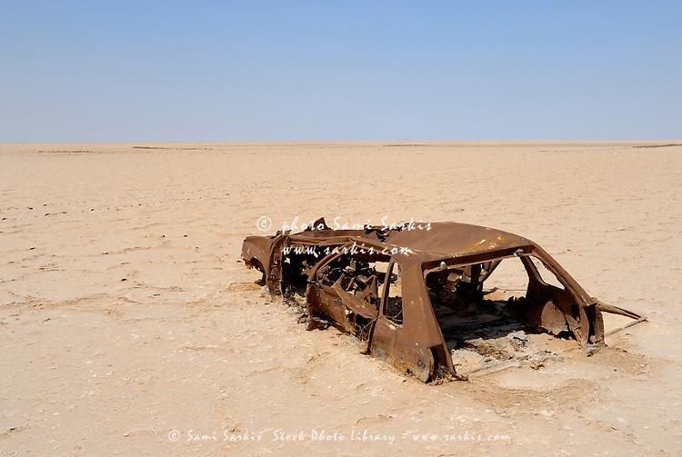 Abandoned and rusty car wreck in desert, Tunisia, Chott el Jerid