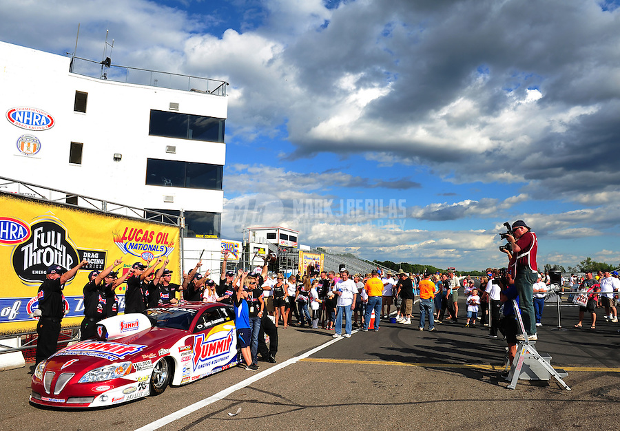 Aug. 21, 2011; Brainerd, MN, USA: Photographers (right) take pictures as NHRA pro stock driver Greg Anderson poses for photographs with his crew after winning the Lucas Oil Nationals at Brainerd International Raceway. Mandatory Credit: Mark J. Rebilas-