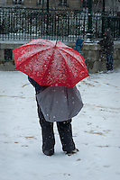 A mother under a red umbrella watches her children play in the snow in a Paris park.