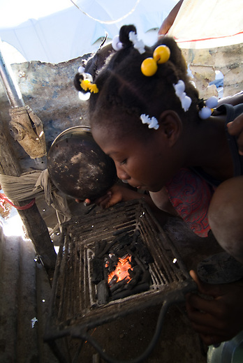 Jeans little sister Silione is preparing the charcoal for cooking in front of the tent. Charcoal is used for cooking in haiti because of very few people can affort the price of gas and it's installations.