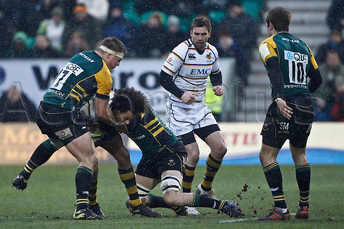 04.02.2012.  Northampton, England. Richard HAUGHTON of London Wasps is tackled by Alex WALLER (left) and Mark SORENSON of Northampton Saints (right) during the LV= Cup match between Northampton Saints and London Wasps at Franklin's Gardens.