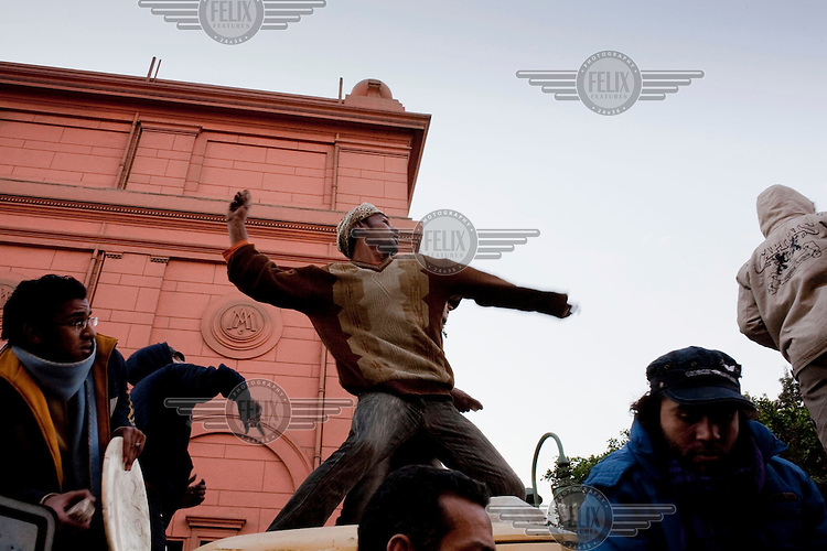 Anti-government protesters throw stones at pro-Mubarak supporters outside the Egyptian Museum in Tahrir Square. Continued anti-government protests take place in Cairo calling for President Mubarak to stand down. After dissolving the government, Mubarak still refuses to step down from power.