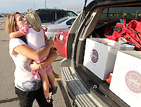 Heather Jacobs takes a break from packing the family SUV to hug her daughter, Ella, 3, during an evening of shuttling her five children to activities in Ankeny.   Heather lost her husband, Eric, in a plane crash in 2006 when she was eight months pregnant with their youngest, Ella, and has since been raising her five young children on her own.