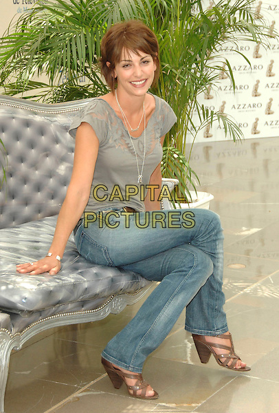 """NOEMIE ELBAZ.attends a photocall promoting the television series """"Femmes de Loi"""" on the fifth day of the 2008 Monte Carlo Television Festival held at Grimaldi Forum, in Monte Carlo, Principality of Monaco, June 12, 2008. .full length sitting grey top jeans brown shoes strappy.CAP/TTL .©TTL/Capital Pictures"""