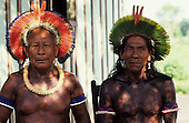 Altamira, Brazil. Two Kayapo Indian elders with bead amulets and tooth necklace wearing feather cocaa headdresses.