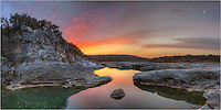 With the moon rising in the east, this sunrise panorama of Pedernales Falls in the Texas Hill Country is comprised of several images stitched together. I often like to merge photos so the viewer can see what I saw - the wide angle view of a beautiful morning. Along this river basin, the water was calm and offered a mirror-like reflection of the colorful sky above.