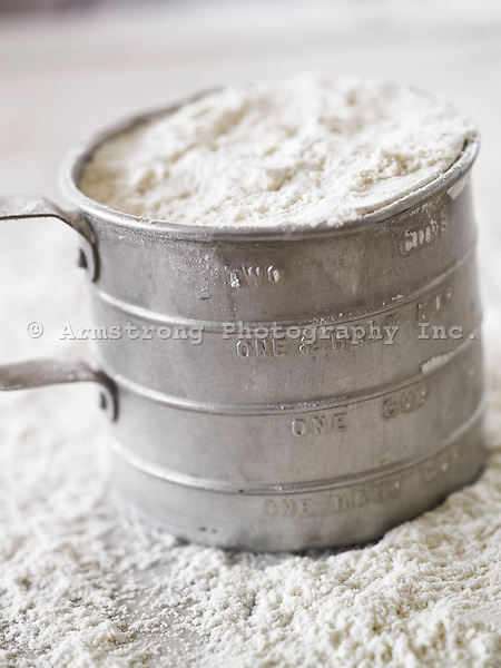 An old-fashioned tin measuring cup filled with white flour