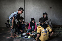 In this Sunday, Sep. 29, 2013 photo, AHMED ABU ABDU sit with his sons and daughter, among them ABDU EL KADER, to take a lunch meal at their family house in Madaya village after attended classes in the public school in the Idlib province countryside of Syria. Children have come back to school in the rebel controlled territory despite the constant threaten of shelling and the ongoing fighting, and public schools still operating financially under the Syrian government administration. (AP Photo)