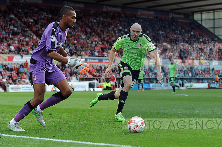 Swindon Town goalkeeper Lawrence Vigouroux is  Conor Sammon of Sheffield United challenged by<br /> - English League One - Swindon Town vs Sheffield Utd - County Ground Stadium - Swindon - England - 29th August 2015