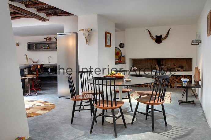 The spacious open plan living room contains a kitchen and dining area, the latter furnished with traditional dining chairs around a retro style table