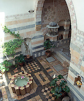 This traditional Syrian courtyard has a dramatic arched entrance