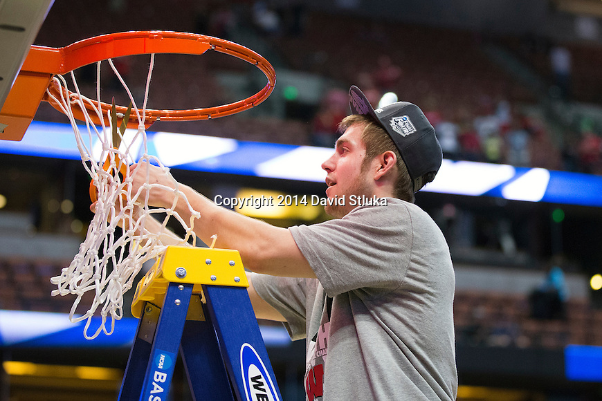 Wisconsin Badgers Jordan Smith cuts down a piece of the net after the Western Regional Final NCAA college basketball tournament game against the Arizona Wildcats Saturday, March 29, 2014 in Anaheim, California. The Badgers won 64-63 (OT). (Photo by David Stluka)