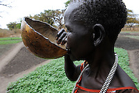 SOUTH-SUDAN Rumbek , village, Colocok, Dinka woman drinks water from calabash, black and white plastic necklace / SUED SUDAN, Rumbek,  Dorf Colocok, Dinka Frau trinkt Wasser aus Kalabasse, schwarz weisse Plastik Halskette