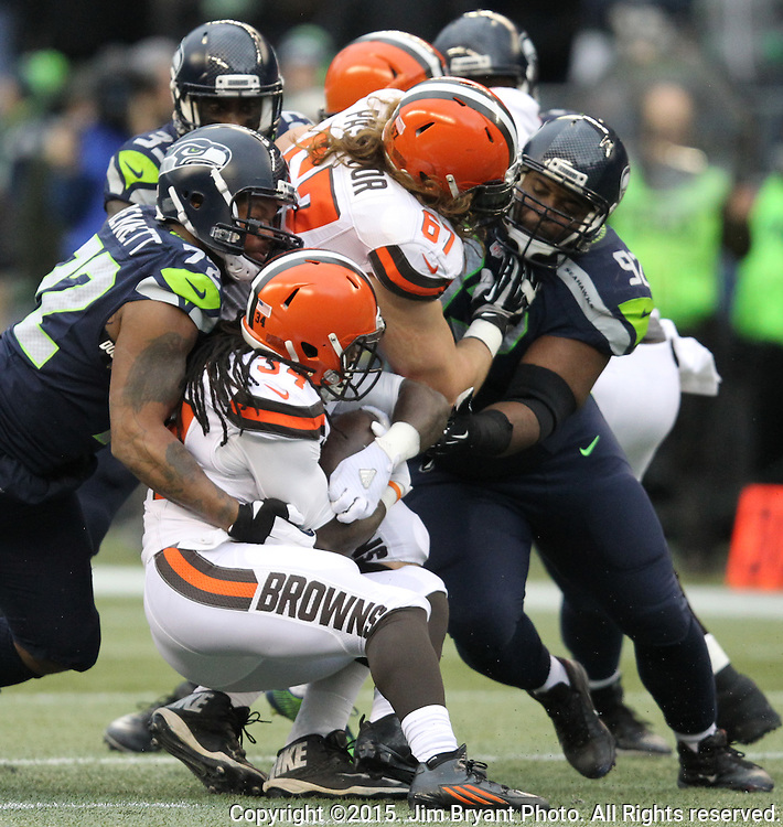 Seattle Seahawks linebacker Michael Bennett (72) and  and  defensive tackle Michael Mebane (92) stops Cleveland Browns running back Isaiah Crowell (34) at CenturyLink Field in Seattle, Washington on December 20, 2015. The Seahawks clinched their fourth straight playoff berth in four seasons by beating the Browns 30-13.  ©2015. Jim Bryant Photo. All Rights Reserved.