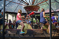 A human-powered bicycle carousel from about 1897, one of only two still around, at Fete Paradiso (Fête Paradiso) on Governor's Island in New York seen on Saturday, August 17, 2013. The festival features 19th and early 20th century vintage French carnival rides and games from the collections of Francis Staub and Regis Masclet. The rides and games are museum quality and this is the first time they have been collected together in one place. Visitors will be able to ride many of them until the exhibit festival closes on September 29, 2013. (© Frances M. Roberts)