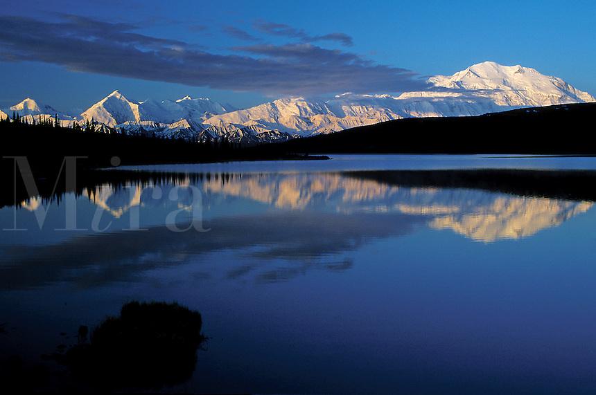 Landscape of Mount McKinley reflected on Wonder Lake. Color contrast in blue of sky, white of mountains and black coastline. Denali National Park, Alaska.