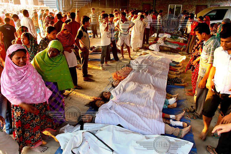 Relatives gather next to the bodies of some of the hundreds of workers killed in the collapsed Rana Plaza complex which are lined up on the floor, covered with white sheeting.The 8 storey Rana Plaza complex, which housed a number of garment factories employing over 3,000 workers, collapsed on 24 April 2013. By 29 April, at least 380 were known to have died while hundreds remained missing. Workers who were worried about going to work in the building when they noticed cracks in the walls were told not to worry by the building's owner, Mohammed Sohel Rana, who is a member of the ruling Awami League's youth front. He fled his home and tried to escape to neighbouring India after the building collapsed but was caught by police and brought back to Dhaka. Some of the factories working in the Rana Plaza building produce cheap clothes for various European retailers including Primark in the UK and Mango, a Spanish label. The final death toll was 1,127. /Felix Features