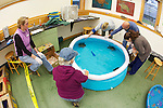 Volunteers With Green Turtles In Pool Warming Up