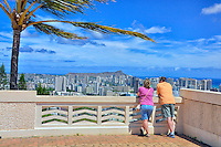 A couple enjoys the view of Diamond Head and Waikiki from a Punchbowl National Memorial Cemetery lookout, Honolulu, O'ahu.