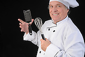 Mature chef in whites working with his utensils stock photo