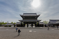 Tourist walk across the gravel filled grounds of Higashi Hongan ji Temple, Kyoto, Japan. Sunday April 24th 2016