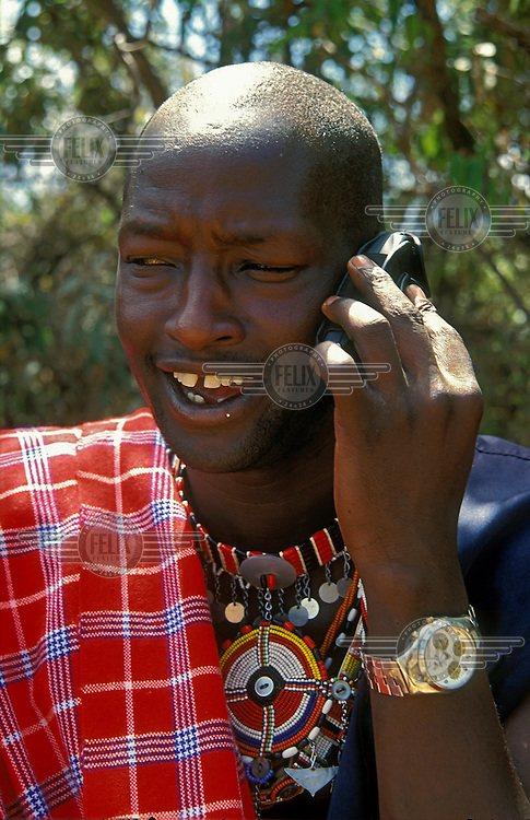 A Maasai man in traditional dress, and wearing a large watch, speaks on his mobile phone.