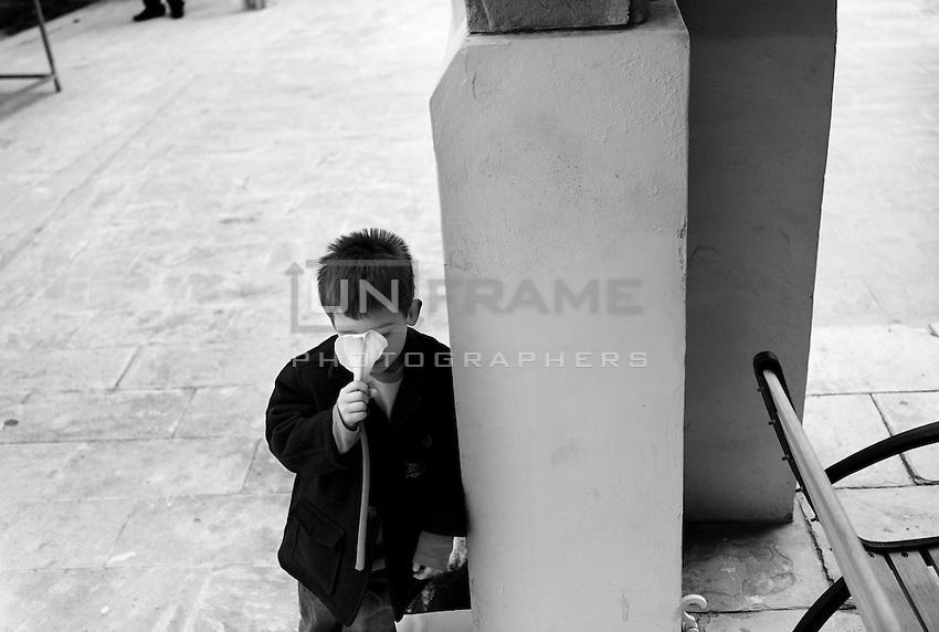 A Greek Cypriot boy smells a lilly after church service