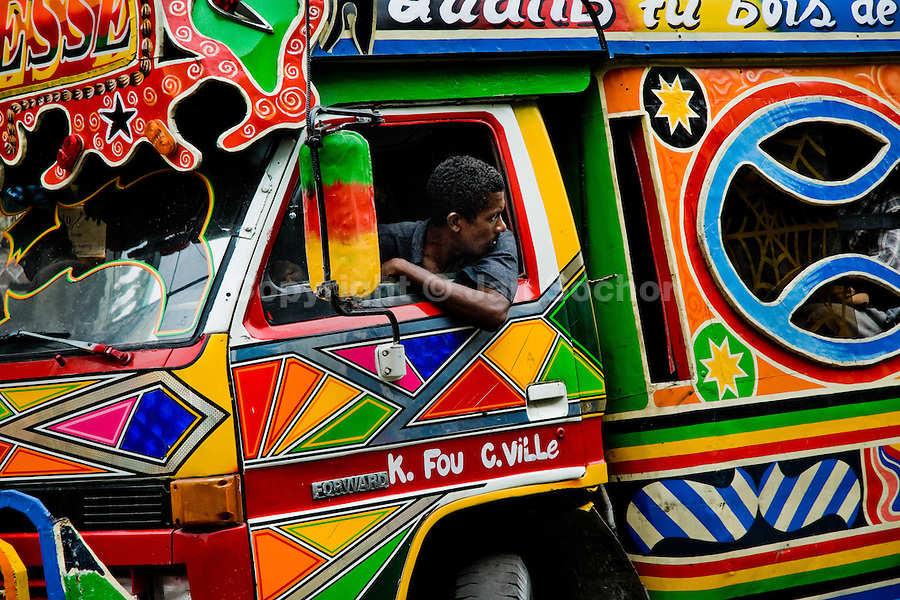 The tap-tap bus driver maneuvers his vehicle in heavy traffic of Port-au-Prince, Haiti, 24 July 2008. Tap-tap vehicles serve as public transportation in Haiti. They are private, operate over fixed routes, departing only when full. Tap-taps are decorated with bright and shiny colors and with a lot of fancy designed elements. There are scenes from the Bible, Christian slogans, TV stars or famous football players often painted on a tap-tap body. Tap-tap name comes from sound of taps on the metal bus body signifying a passenger's request to be dropped off.
