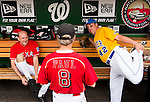 Rep. Louie Gohmert, R-Texas, left, slips on a knee brace as Rep. Jeff Duncan, R-S.C.., right, stretches while talking with Sen. Rand Paul, R-Ky., in the Republicans' dugout before the 52nd annual Congressional Baseball Game at national Stadium in Washington on Thursday, June 13, 2013.