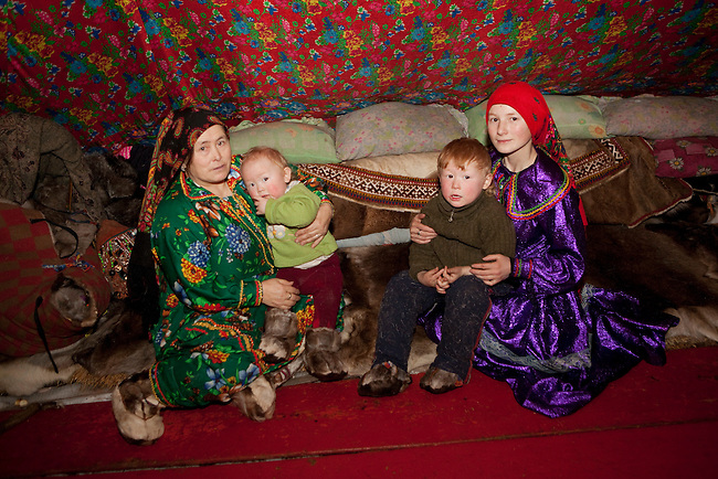 Kristina Neyva (right), a young Khanty woman, with her young sons and Lydia, her mother-in-law (left) Vadim, in their tent at a winter reindeer herders' camp. Yamal, Western Siberia, Russia