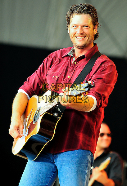 "BLAKE SHELTON .Country music star BLAKE SHELTON performs on opening day of ""Jamboree In The Hills 2010"" also known as the ""Super Bowl of Country Music"", Morristown, Ohio, USA..July 15th, 2010                              .stage concert live gig performance music half length red shirt guitar jeans denim .CAP/ADM/RP.©Ryan PavlovAdMedia/Capital Pictures."