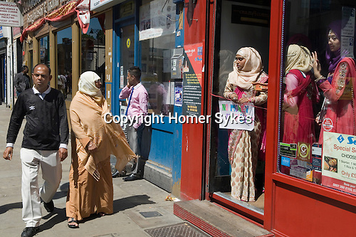 """Muslim women Brick Lane London wait for wedding guests to enter a restaurant. The sign she holds reads """"No Money No Honey"""", a tradition in Bengali wedding for the brides relatives to tease the groom into giving a small gift of money."""