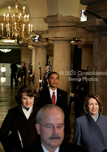Washington, DC - January 20, 2009 -- United States President-elect Barack Obama walks through the U.S. Capitol crypt behind U.S. Senator Dianne Feinstein (Democrat of California) and  Speaker of the U.S. House of Representatives Nancy Pelosi (Democrat of California) on his way to being sworn in as the 44th President of the United States during the inaugural ceremony in Washington, Tuesday, January 20, 2009.   .Credit: Molly Riley - Pool via CNP