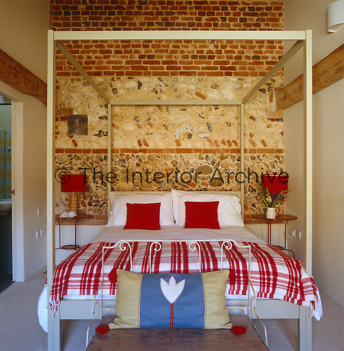 This bedroom, furnished with a simple four-poster bed, has exposed walls that are a mixture of brick, flint and chalk that are rich in texture