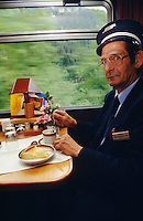 The conductor of Glacier Express enjoying coffee and cake.