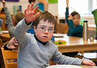 Non-disabled and disabled students (in this case a boy suffering from Down's syndrome) learn together in the same class in a primary school.