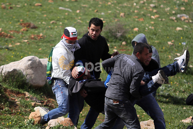 Palestinian protesters carry a wounded man during clashes in front of Ofer prison, near the West Bank city of Ramallah, following a demonstration in support of Palestinian detainee, Samer Issawi, who has been on hunger strike for more than 200 days, and other prisoners on hunger strike in Israeli prisons on February 15, 2013. A United Nations official on February 13, expressed concern about the wellbeing of Palestinian detainees in Israeli prisons and in particular about the condition of Issawi. Photo by Issam Rimawi