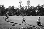 Colm, Marcus' father, shelters Marcus as they watch Brendan run during a soccer lesson.  Colm has always played soccer and enjoys sharing that with Brendan.  Colm works long hours to support his family, so Marcus stays close to him whenever he is home.