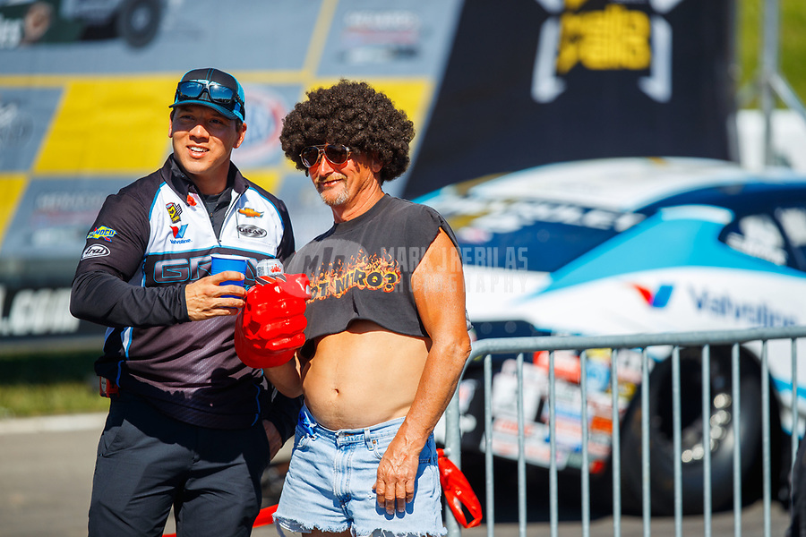 May 21, 2017; Topeka, KS, USA; Dave Connolly (left), crew chief for NHRA pro stock driver Tanner Gray poses for a photo with a fan during the Heartland Nationals at Heartland Park Topeka. Mandatory Credit: Mark J. Rebilas-USA TODAY Sports